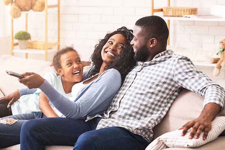 Family Sitting on Couch with TV Remote Smiling