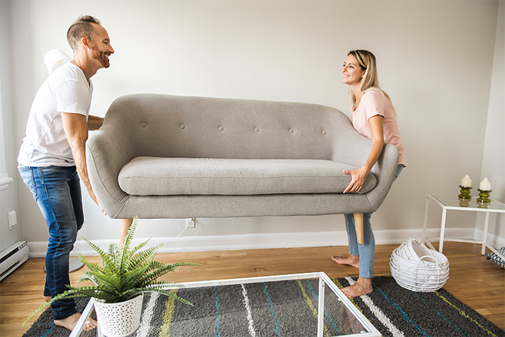 couple-moving-couch-in-living-room