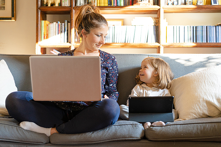 mom-and-daughter-using-laptops-on-couch