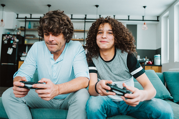 Two brothers playing video games on the couch