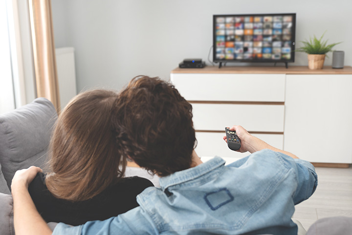 A couple searching for a movie to stream on their tv