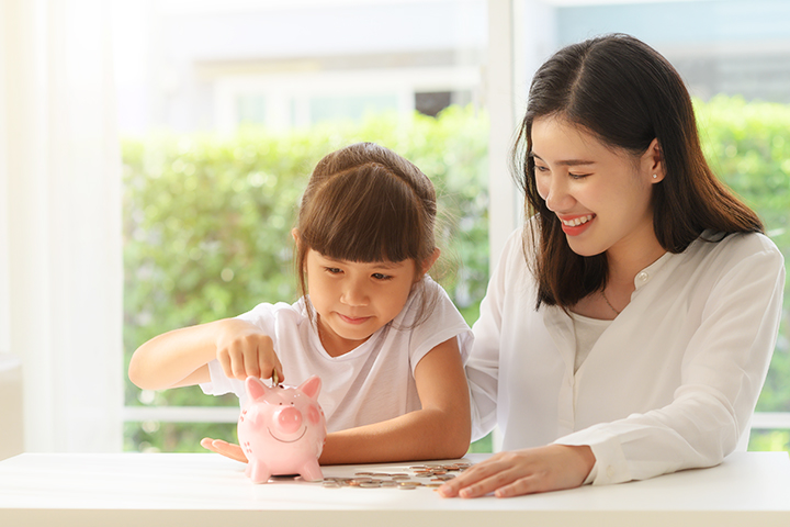Mom and daughter putting money into piggybank to save