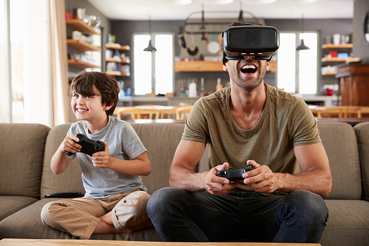 Dad and son using internet to play video games with VR headset