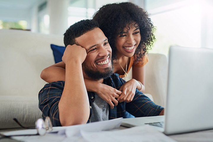 Couple smiling at laptop and internet perks