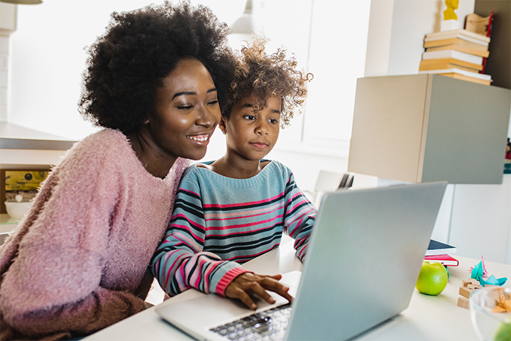 A mother helps her child with online school